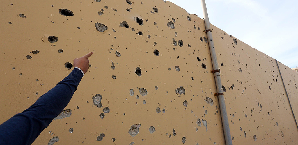 A man points at impact holes on the wall at the entrance of Tripoli's Corinthia Hotel where gunmen blew themselves up after killing at least nine people, January 28, 2015. (Mahmud Turkia/AFP/Getty Images)