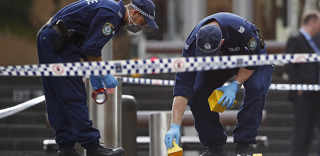 Police officers examine potential evidence near the Lindt Cafe in Sydney, Australia, where a hostage crisis prompted the Australian government to raise its terrorism alert level. December 16, 2014. (Jason Reed/Reuters/Corbis)