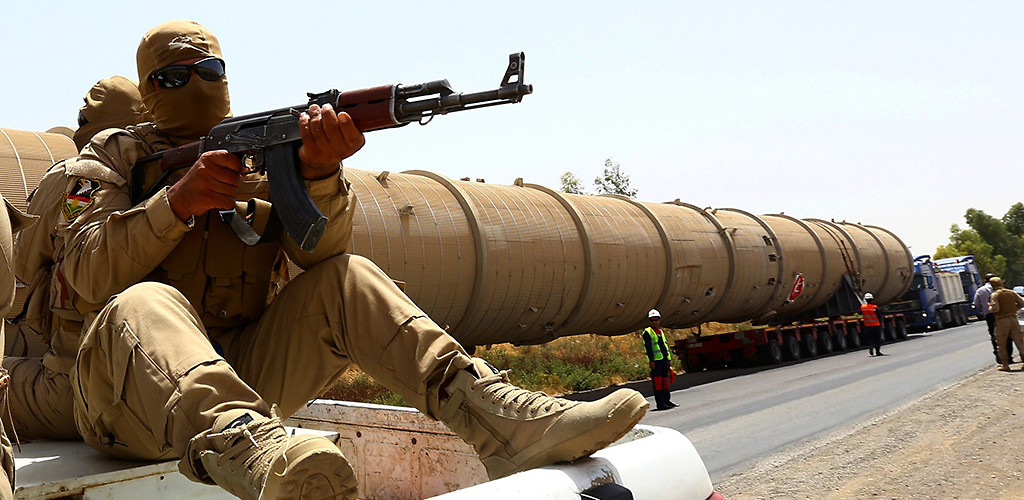 A section of an oil refinery is guarded as it is brought on a truck to the Kawergosk Refinery, some 20 km east of Erbil, the capital of the autonomous Kurdish region of northern Iraq, July 14, 2014. (Safin Hamed/AFP/Getty Images)