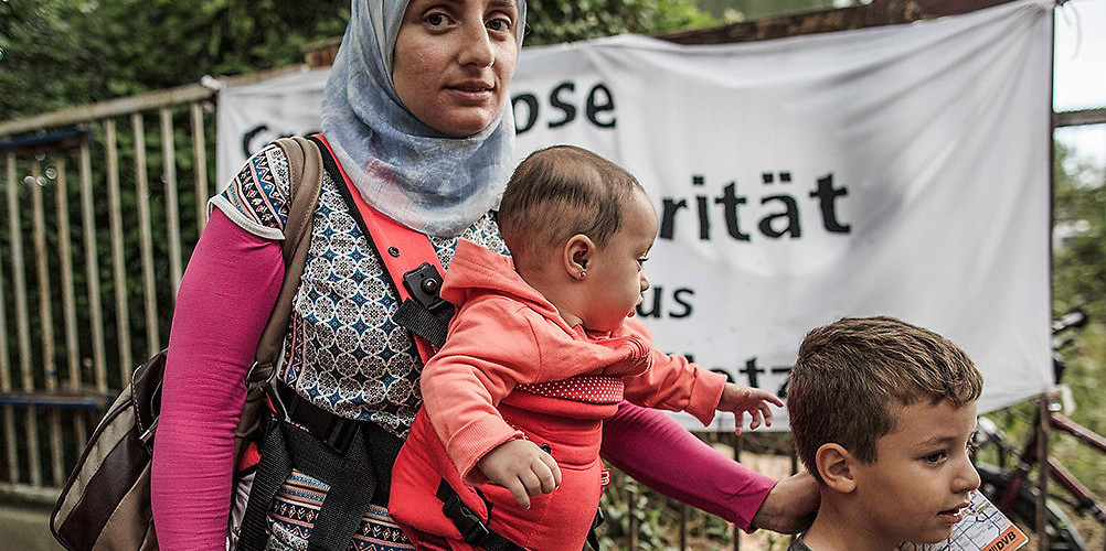 A mother and her children enter a temporary camp for Syrian refugees in Germany. Dresden, Germany, July 27, 2015.  (Carsten Koall/Getty Images)