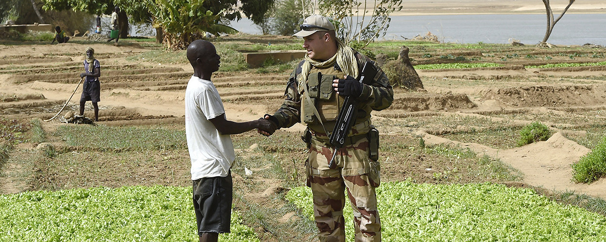 A solider shakes hands with a man at a vegetable garden irrigated with funding from the French army. Gao, Mali, May 30, 2015. (Phillipe Desmazes/AFP/Getty Images)