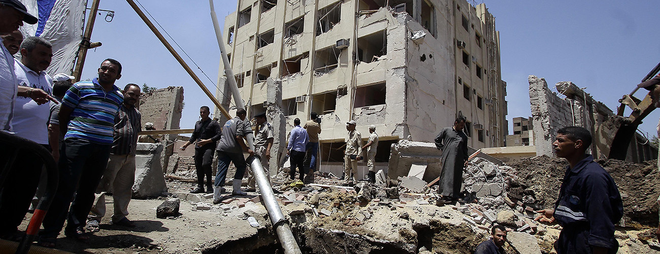 Workers inspect the bombed site of a security building in the Shubra-el-Kheima district. Cairo, Egypt, August 20, 2015. (Ahmed Abd el Fattah/Demotix/Corbis)