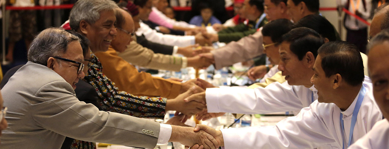 Representatives of Myanmar's government and ethnic armed groups shake hands after an earlier discussion on a ceasefire agreement. Yangon, Myanmar, July 22, 2015. (U Aung/Xinhua/Getty Images)