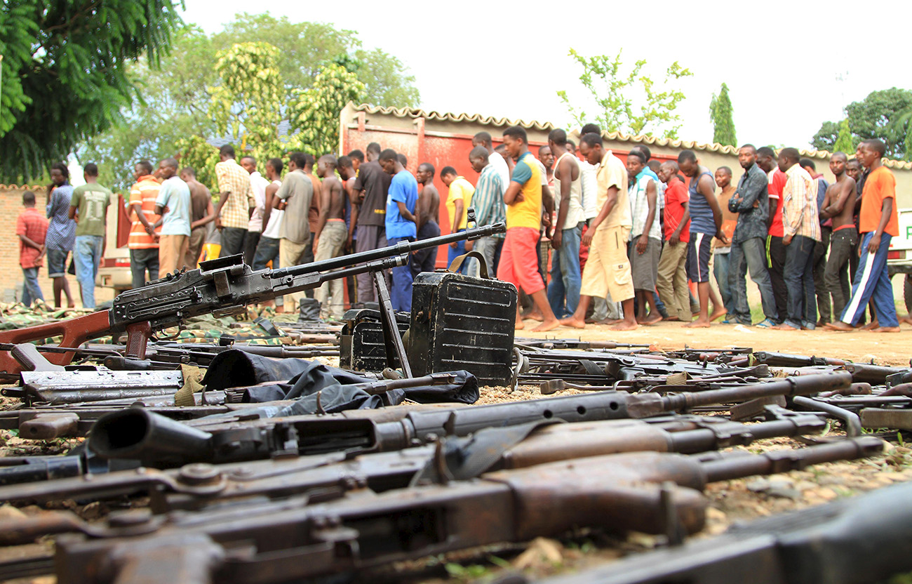 Suspected fighters are paraded before Burundian media near a cache of recovered weapons. Bujumbura, Burundi, December 12, 2015. (Jean Pierre Harerimana/Reuters/Corbis)