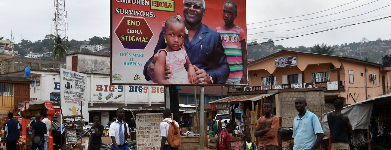 People walk past a sign warning against stigmatization of Ebola victims, which are comparatively fewer than those urging caution. Freetown, Sierra Leone, January 22, 2016. (Sia Kambou/AFP/Getty Images)