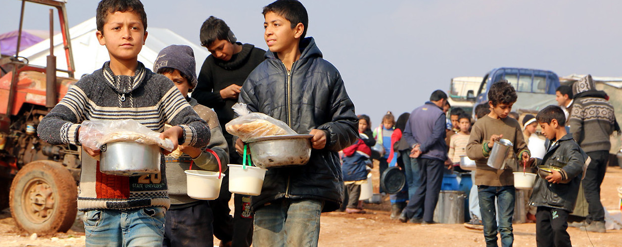 Turkmen children carry food distributed by aid agencies at the al-Ra'ee camp, where they fled after Russian and Syrian bombing of their communities. Aleppo, Syria, January 21, 2015.(Mustafa Sultan/Anadolu Agency/Getty Images)