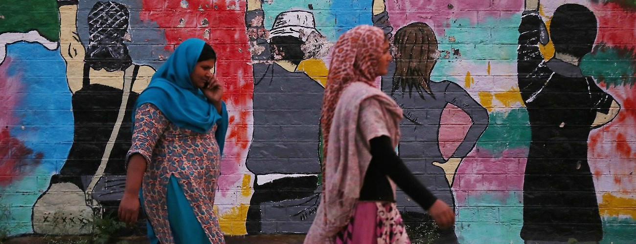 Pakistani women pass by Graffiti's on the exterior wall of a school. Rawalpindi, Pakistan, November 20, 2015. (Metin Aktas/Anadolu Agency/Getty Images)