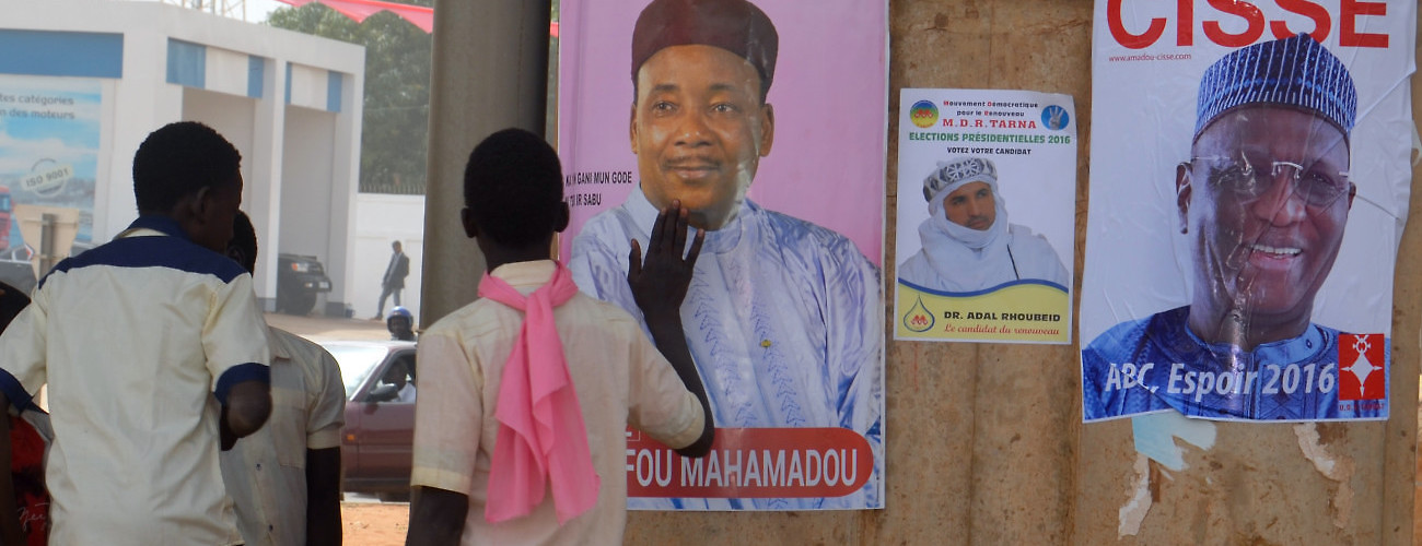 Students walk past campaign posters for Niger's incumbent President and presidential candidate Mahamadou Issoufou and  ex-planning minister Amadou Boubacar Cisse. Niamey, Niger, January 30, 2016. (Boureima Hama/AFP/Getty Images)
