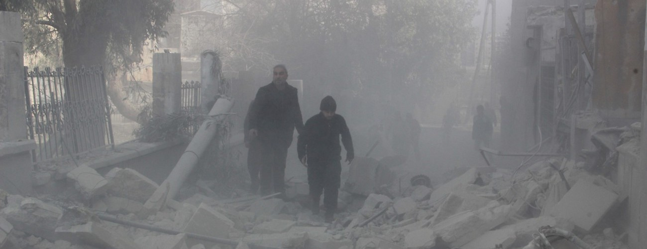 People walk past the rubbles of damaged buildings after the Russian airstrikes targeted residential areas in opposition controlled El Zebdiye neighborhood.  Aleppo, Syria, February 13, 2016. (Ahmed Muhammed Ali/Anadolu Agency/Getty Images)