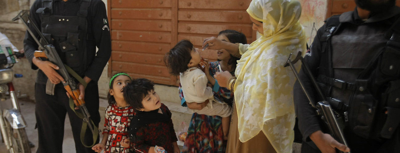 A Pakistani health worker gives a polio vaccine to children under tight security, in Peshawar, Pakistan, Monday, Oct. 24, 2016. (AP Photo/Mohammad Sajjad)