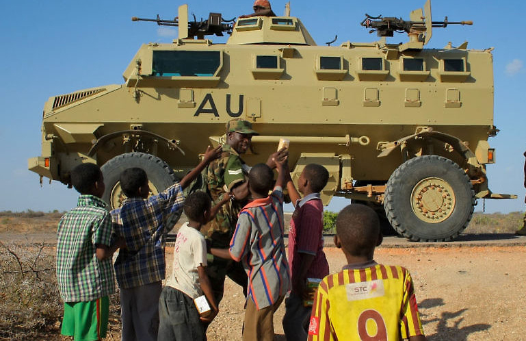 SOMALIA, Buur-Hakba: In a photograph taken and released by the African Union-United Nations Information Support team 28 February 2012, Ugandan soldiers serving with the African Union Mission in Somalia (AMISOM) hand out biscuits to young Somali children in the central Somali town of Buur-Hakba following it's capture the day before from the Al-Qaeda-affiliated extremist group Al Shabaab by the Somali National Army (SNA), supported by AMISOM forces. The strategically important town linking the capital Mogadishu and the hinterlands of central Somalia was liberated without a shot being fired, marking a significant loss for the group. Under the Shabaab's repressive and violent rule, social and leisure past-times such as football were banned in every form including watching and playing. The town, located 64kms east of Baidoa, Somalia's second city, was a stronghold of the Shabaab where they extorted high levies of illegal taxation on the local civilian populations and used it as a base from where they planned and launched attacks against government forces and installations, AMISOM and the Somali population. Buur-Hakba is the latest in a string of notable territorial losses for the extremist group to SNA and AMISOM forces over the last 18 months, which has seen their area of influence and control over towns and areas across Somalia steadily and rapidly decrease. AU-UN IST PHOTO / STUART PRICE.