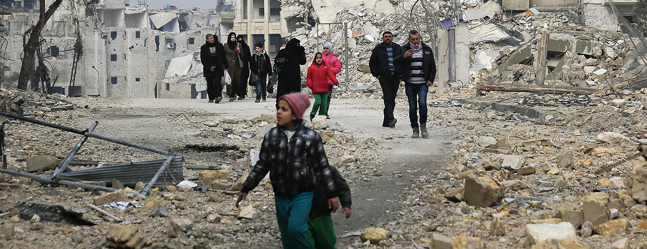 Aleppo residents walk among the rubble of former  apartment buildings. Syria, January 20, 2017. (Hassan Ammar/Associated Press)